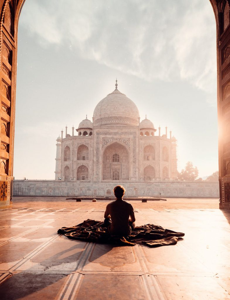 person sitting in front of the taj mahal